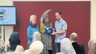 Trustees of the Cardiff Crescent Centre, Donna Sandercock and Edward Seddon, receiving the Peace Mala interfaith dove from the founder of Peace Mala, Pam Evans